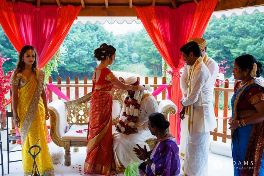 walled garden orchardleigh wedding bride puts garlands on groom