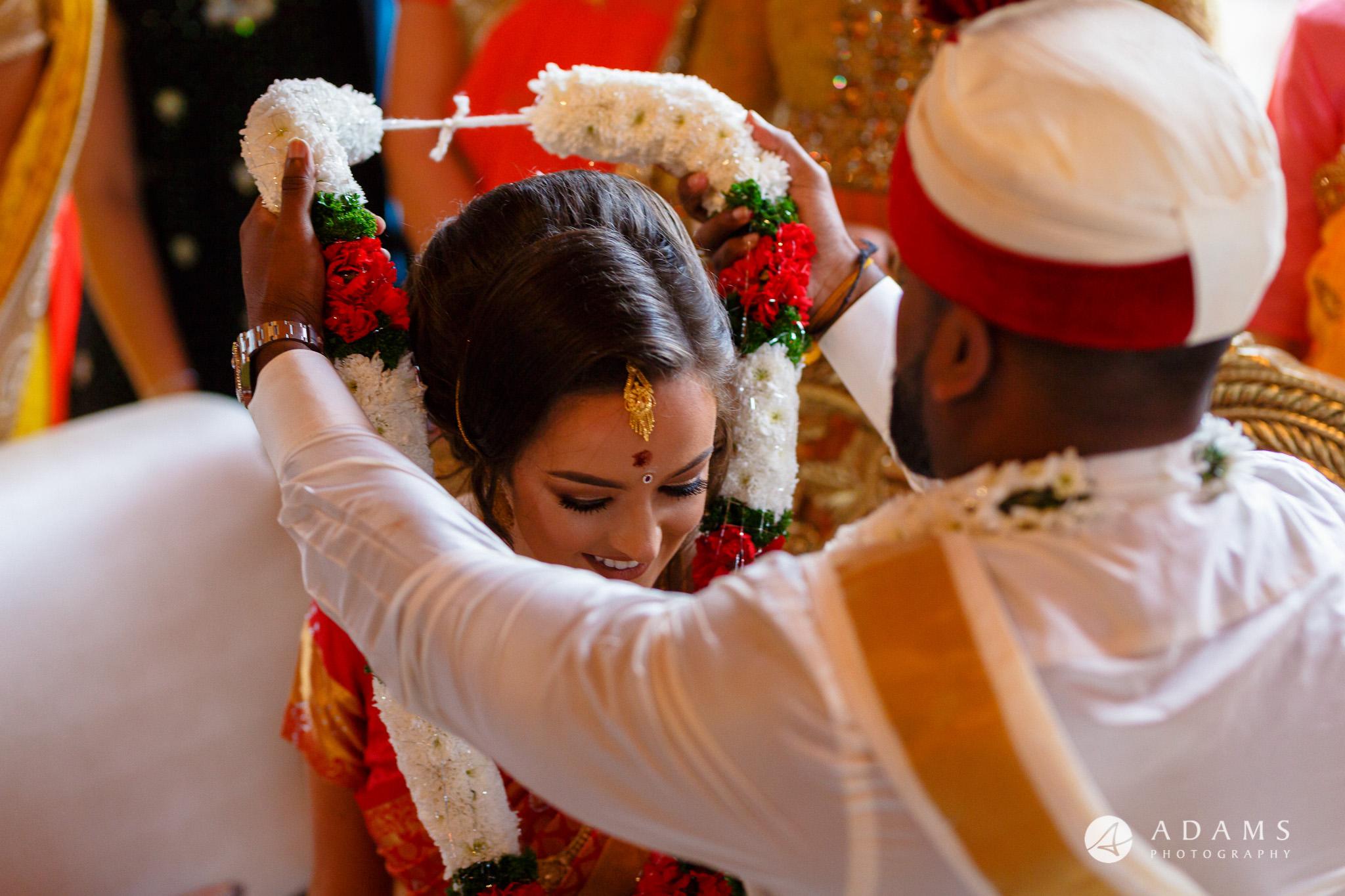 walled garden orchardleigh wedding groom is putting garlands on brides neck