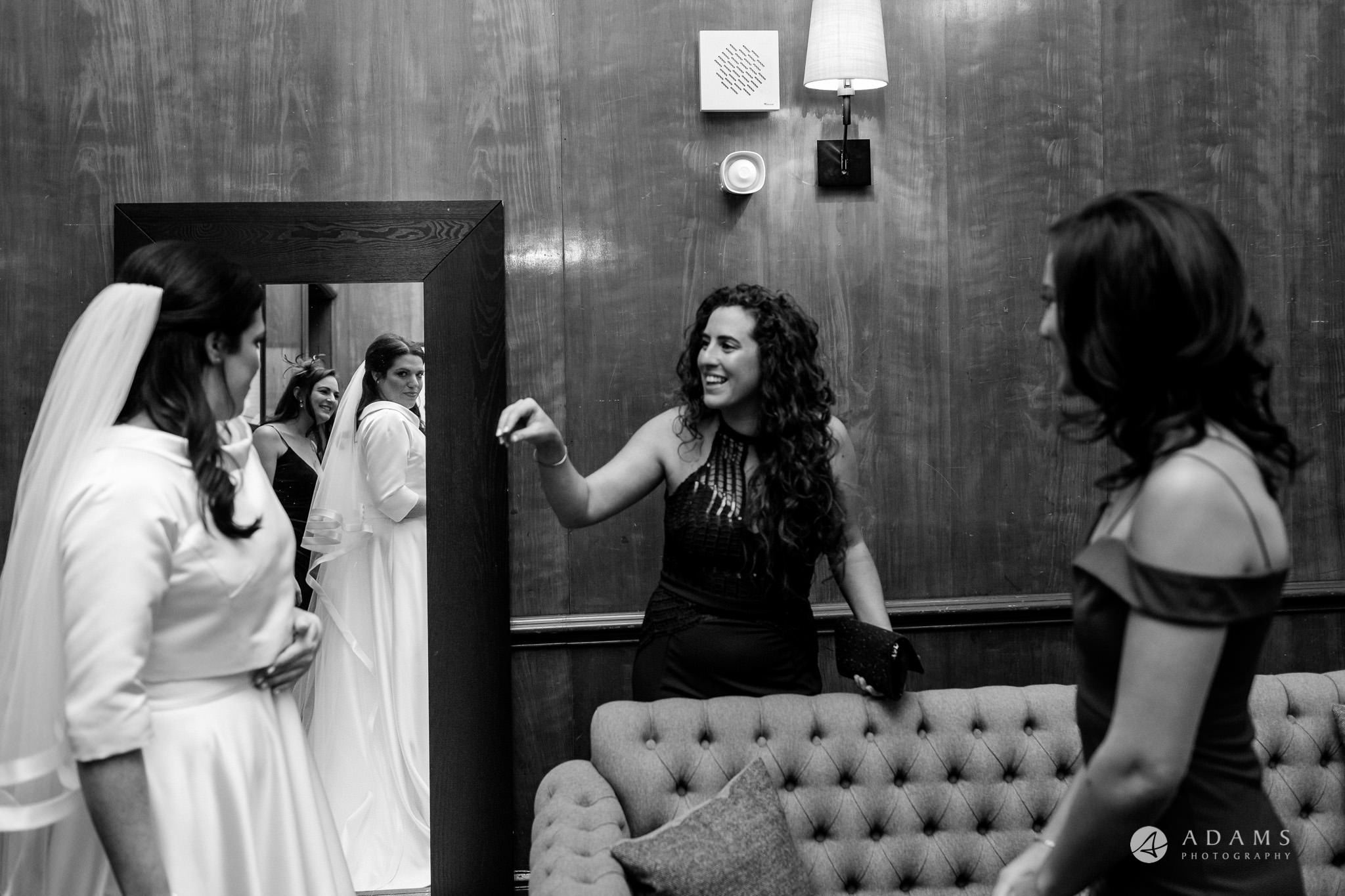 grand connaught rooms wedding bridesmaid is looking on the bride while she is checking herself in the mirror