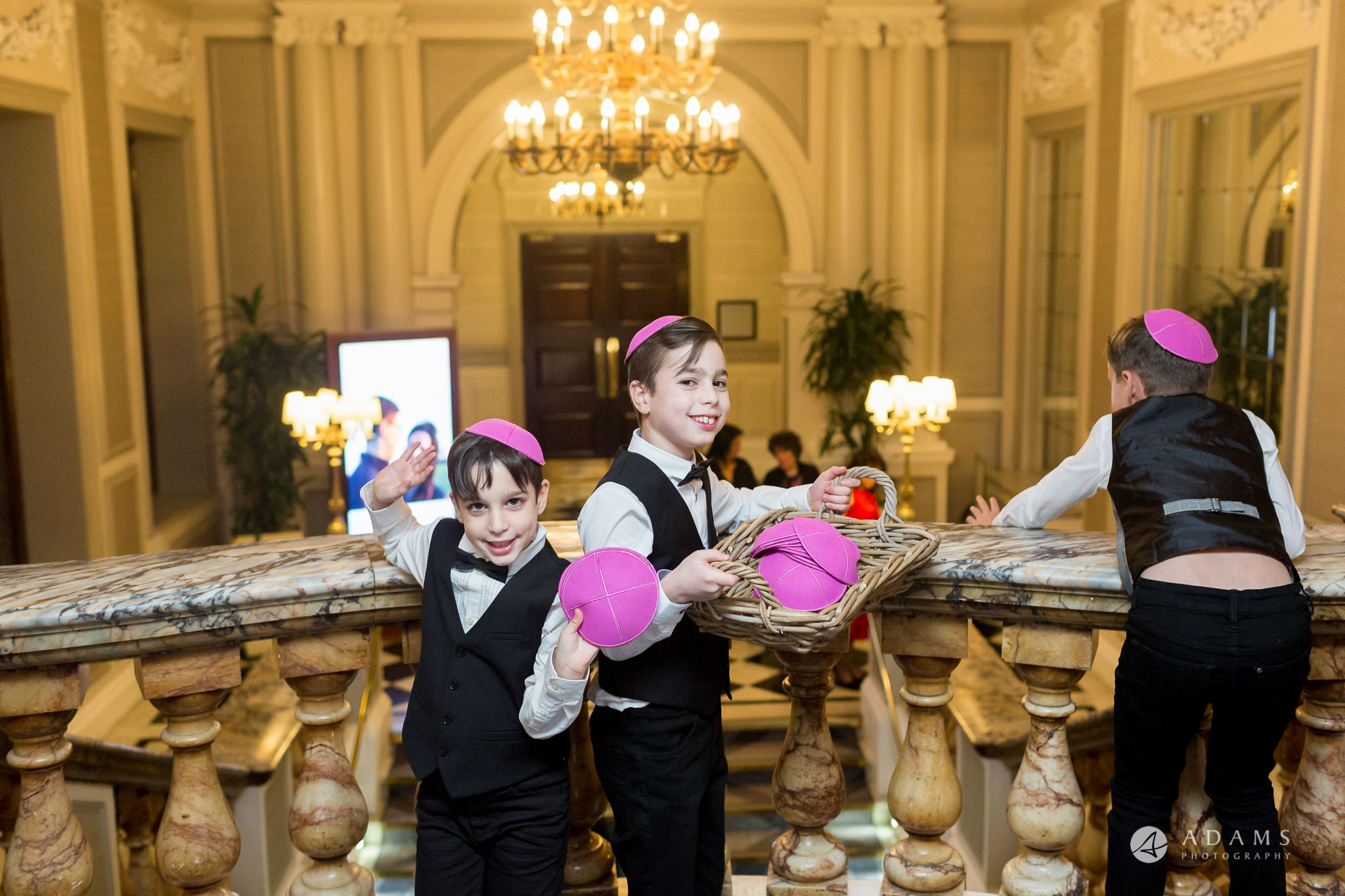 grand connaught rooms wedding boys are holding kippas and giving to the guests