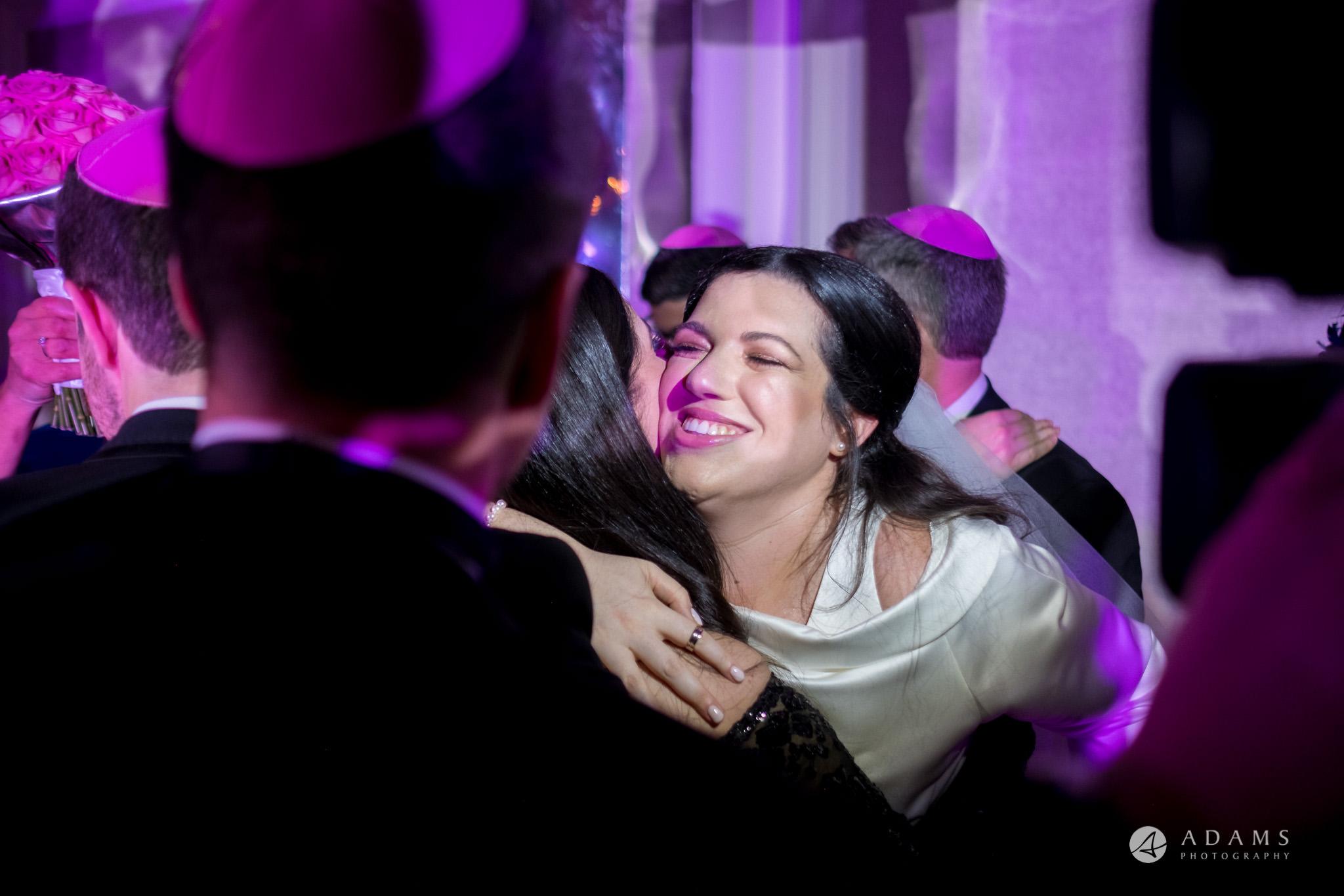 De Vere grand connaught rooms bride hugs her bridesmaid under chuppah