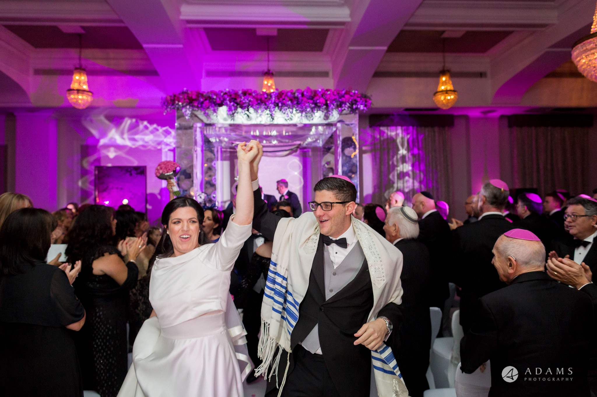 De Vere grand connaught rooms bride and groom leave the chuppah very happy with hand up