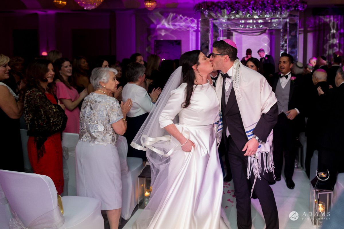 De Vere grand connaught rooms bride and groom kiss each other in front of the chuppah