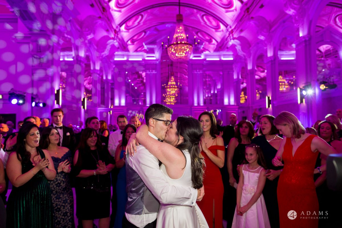 grand connaught rooms wedding couple hugging and kissing in the center of the room