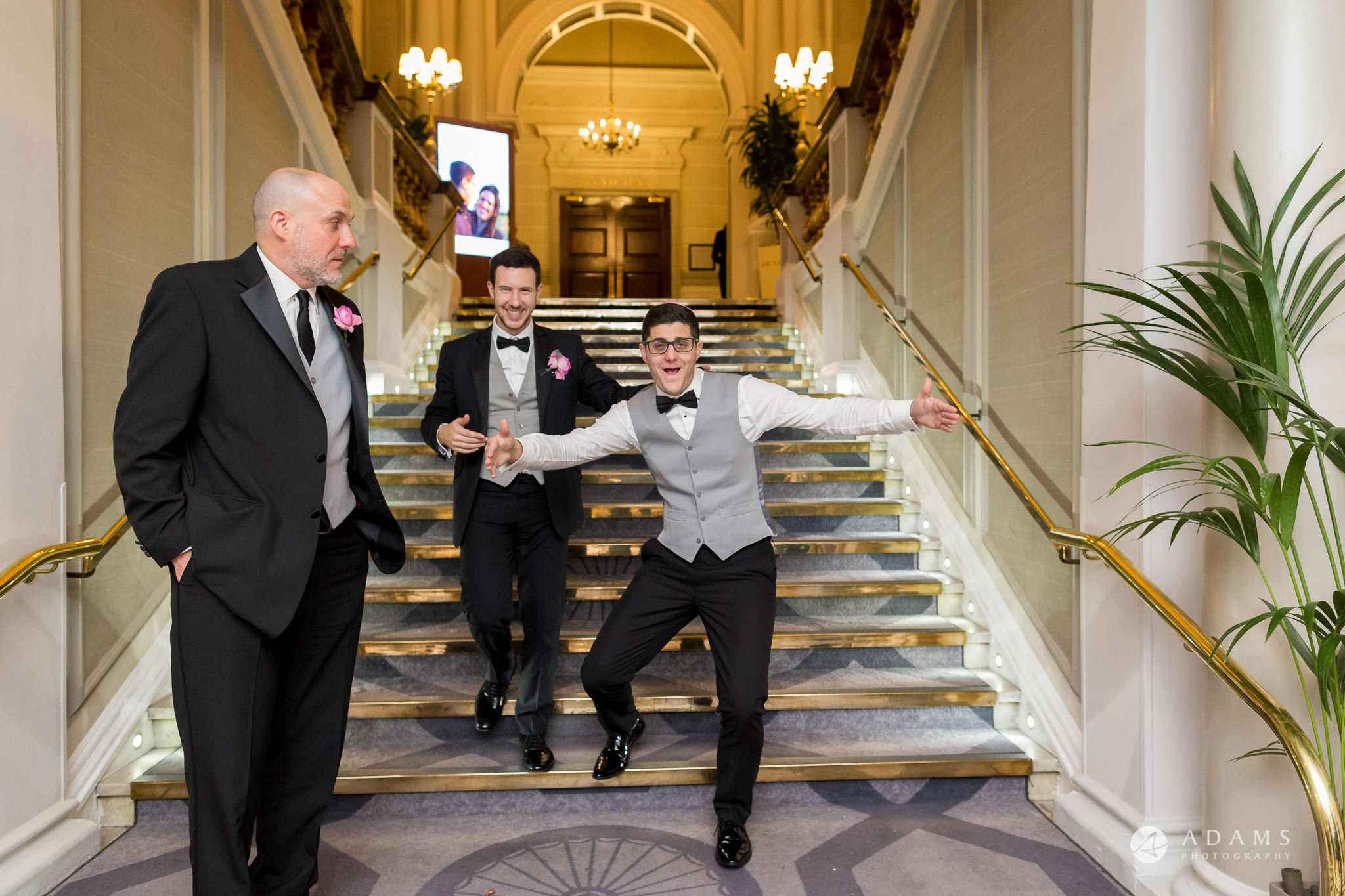 Grand connaught rooms photographer groom and his groomsmen jump on the stairs