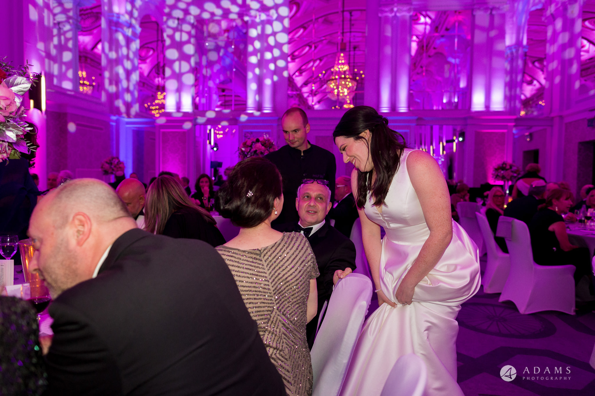 Grand connaught rooms photographer bride welcomes her guests by the table