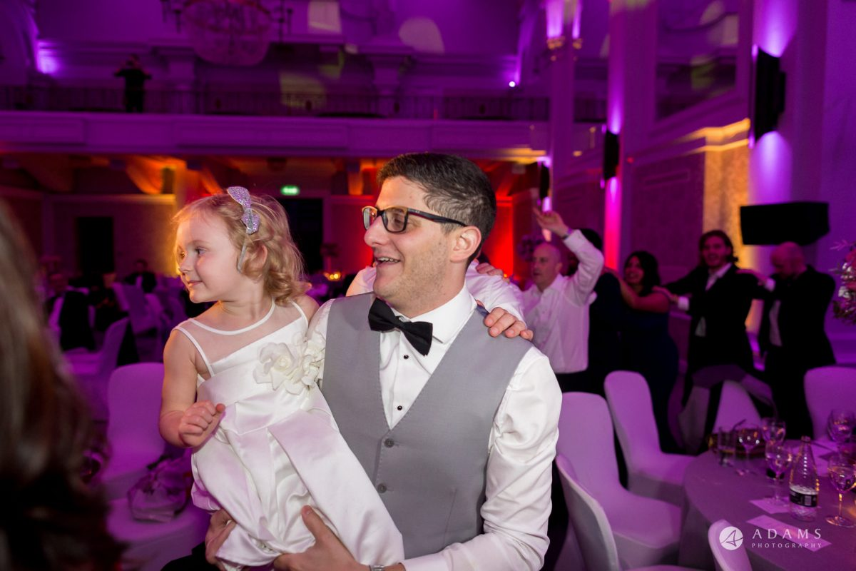 Grand connaught rooms wedding groom holds a small girl on his hands
