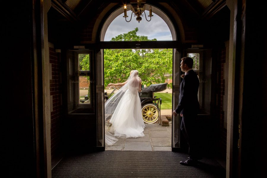 Cinematic wedding videography couple leaving the venue in a classic car