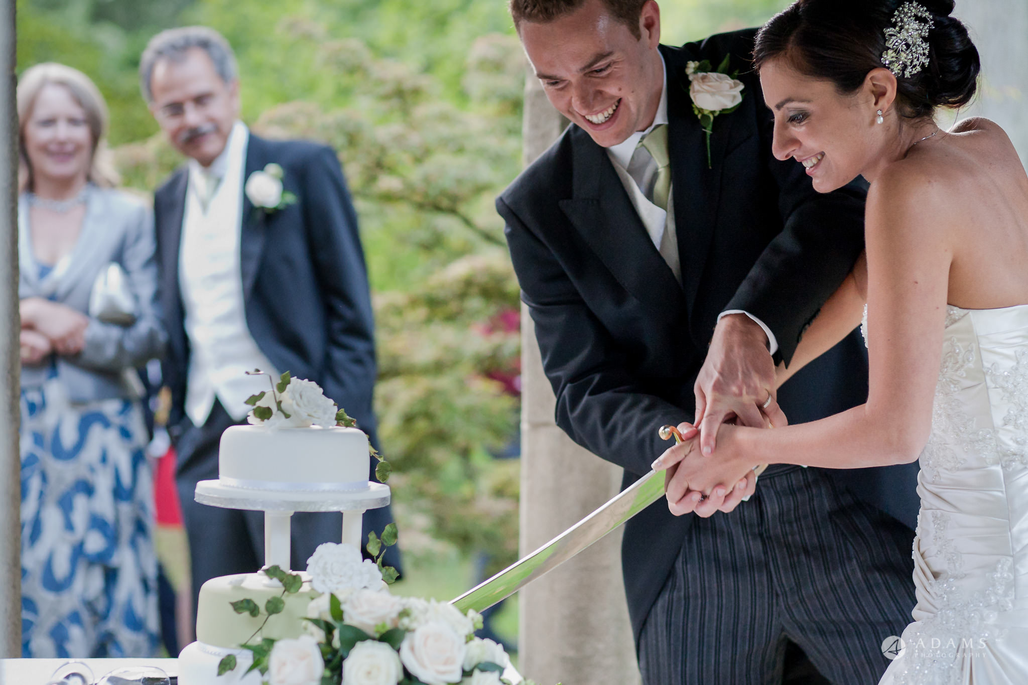 Kingston Bagpuize House wedding cake cutting with a sward
