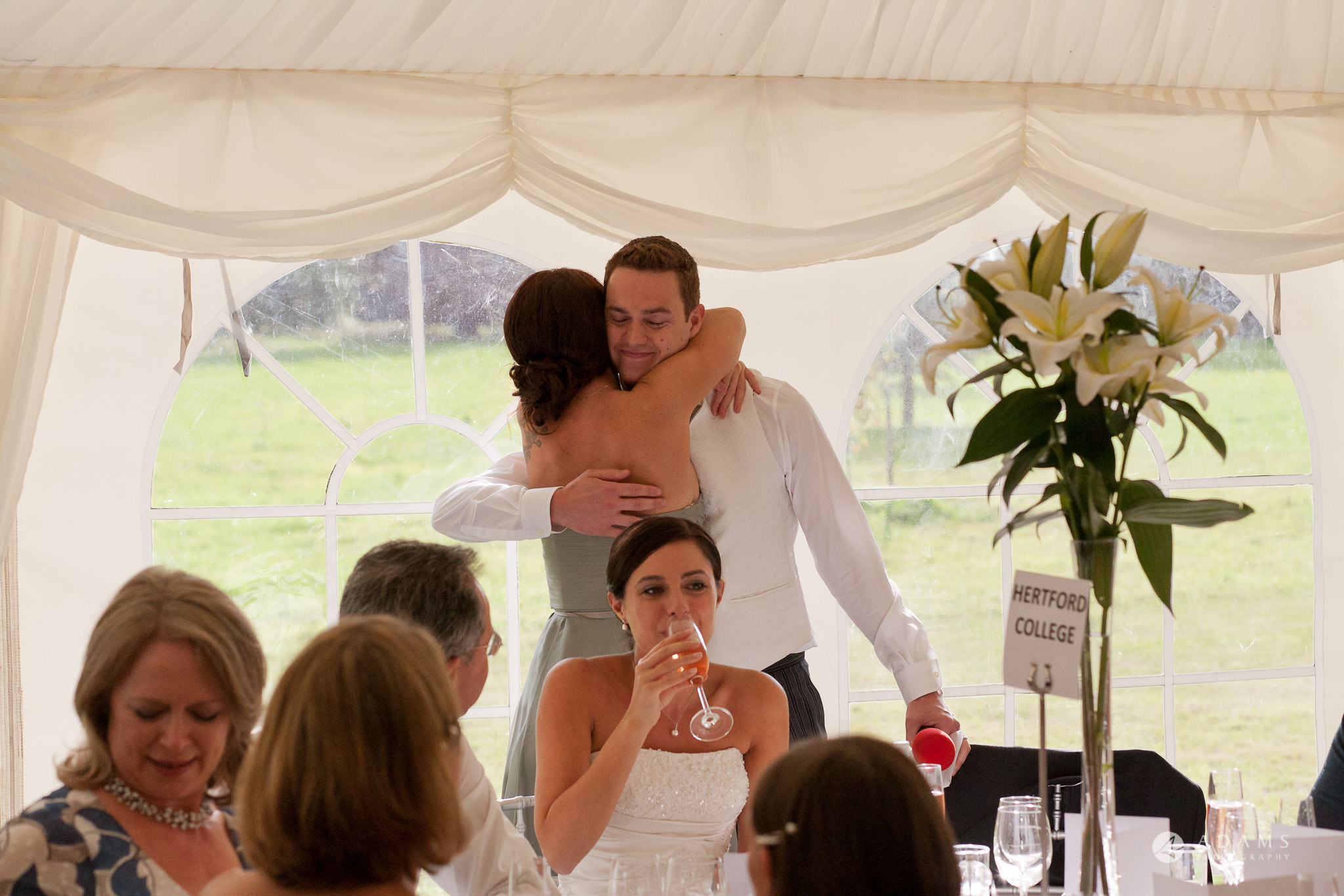 Kingston Bagpuize House wedding groom hugs a bridesmaid