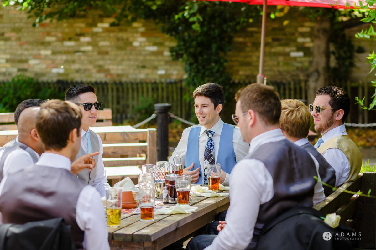 Trinity College Cambridge wedding groom wiht hits friends eating breakfast