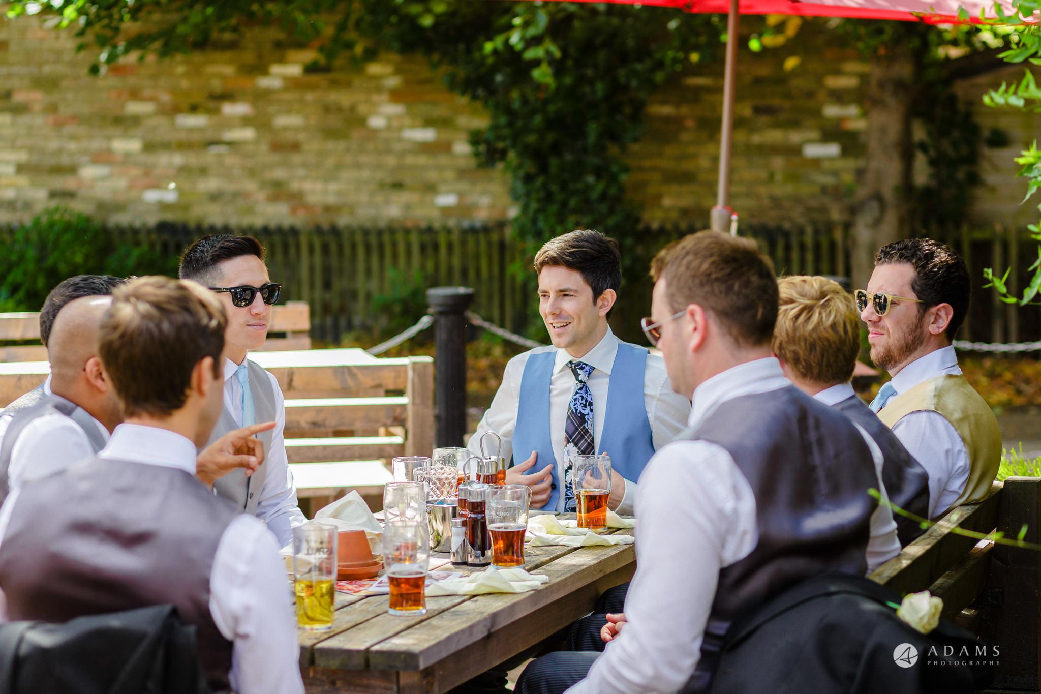 Trinity College Cambridge wedding groom wiht hits friends eating breakfast