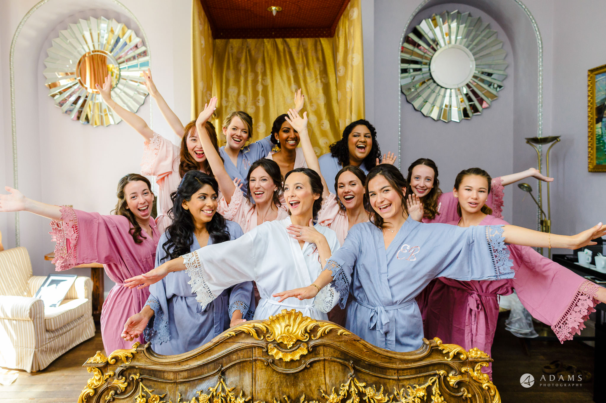 Trinity College Cambridge wedding bridal party on the bed laughing