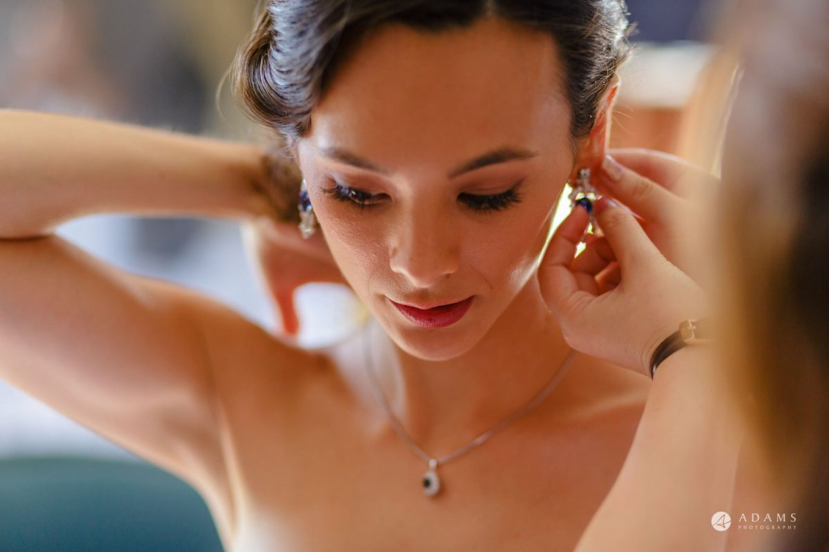 Trinity College Cambridge wedding bride putting earrings