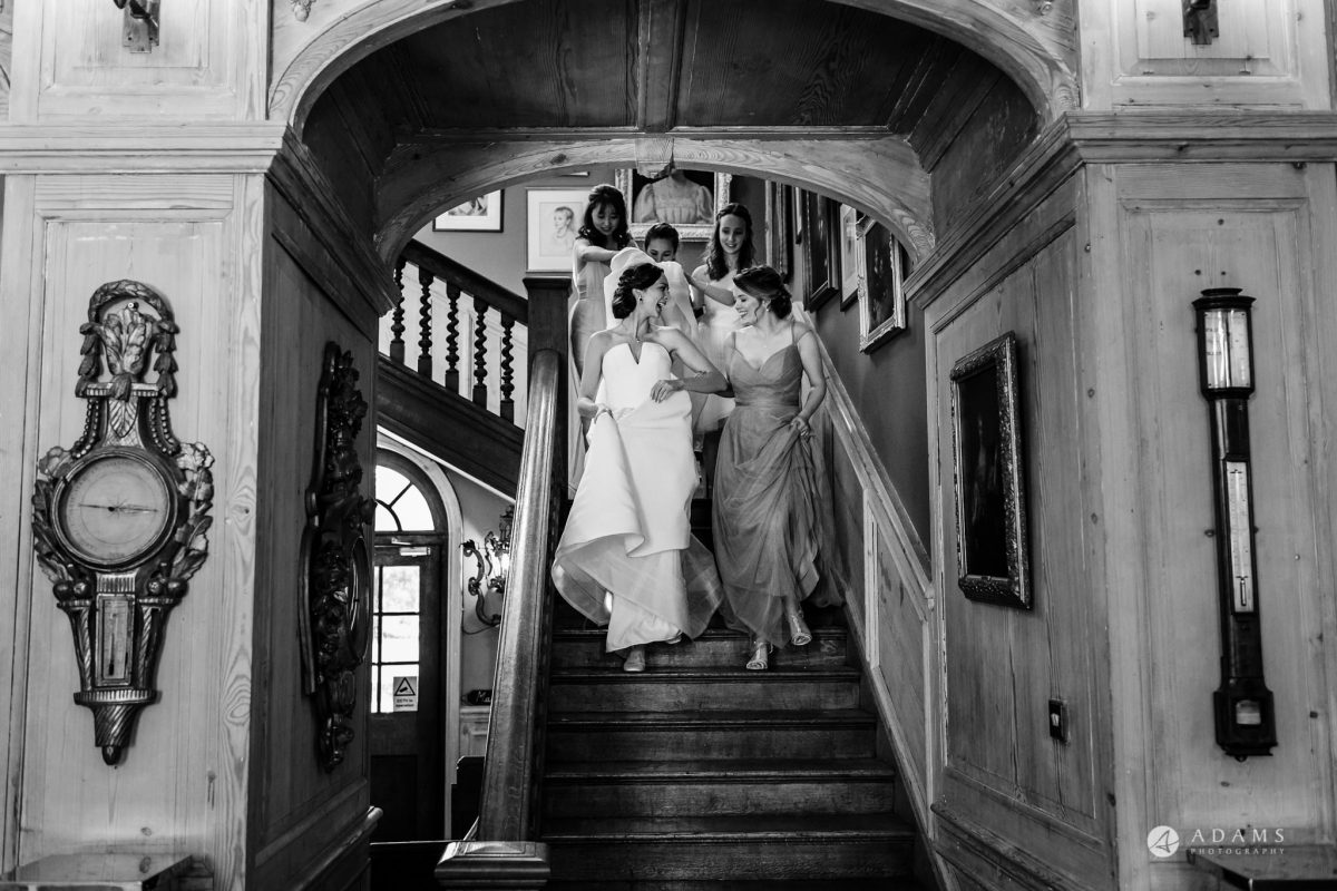 Trinity College Cambridge wedding bride and bridesmaids walk down the stairs