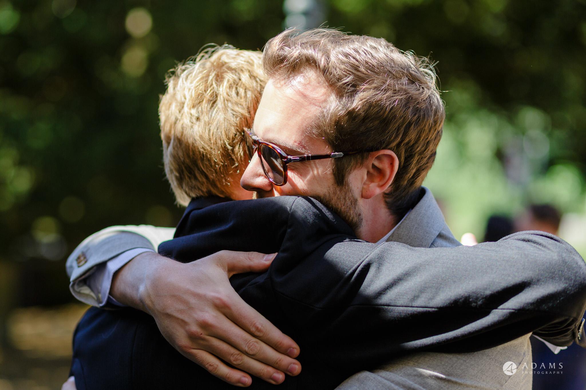 Trinity College Cambridge wedding guests hugging