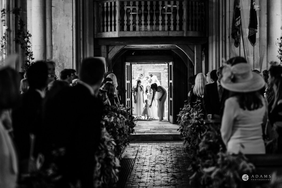 Trinity College Cambridge wedding flower girl enters the church