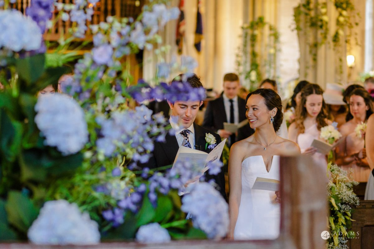 Trinity College Cambridge wedding bride looks at groom during ceremony