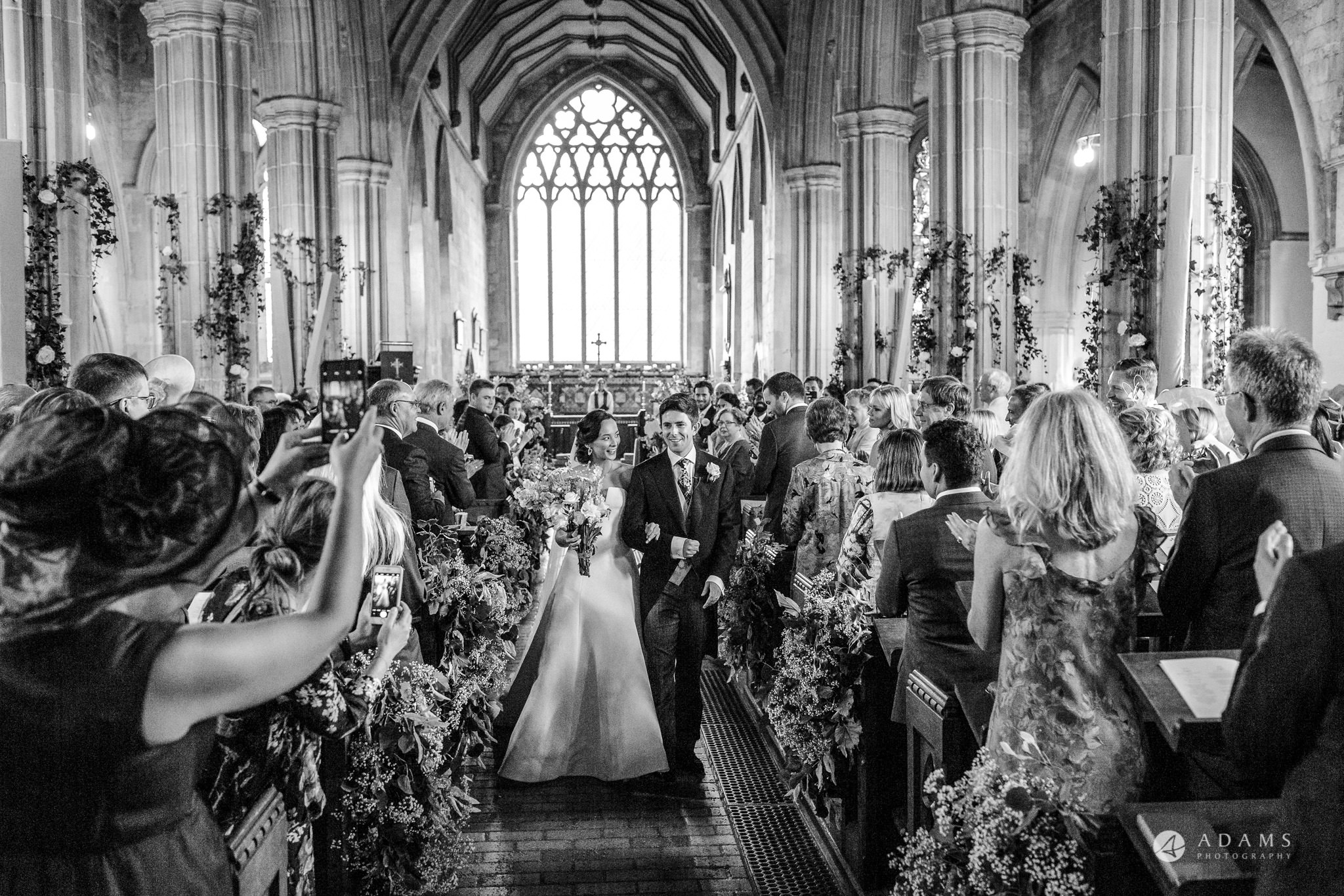 Trinity College Cambridge wedding bride and groom leave the church