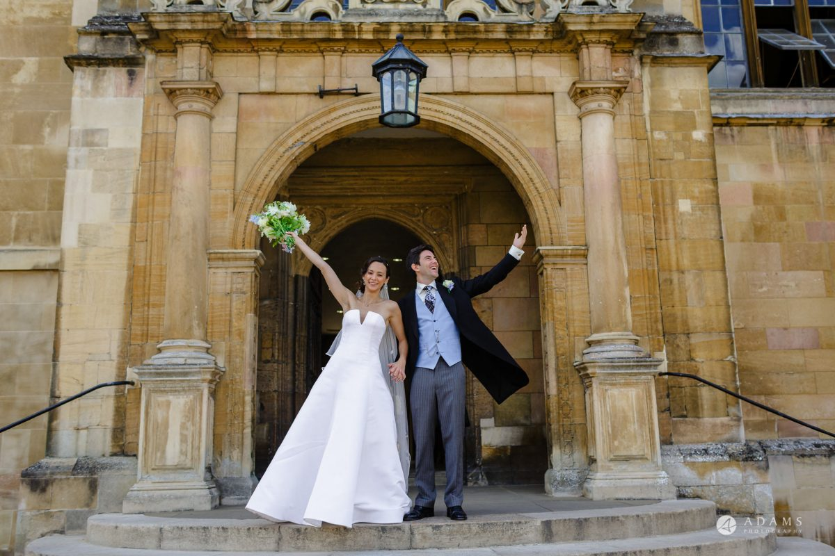 Trinity College Cambridge wedding bride and groom raise their hands