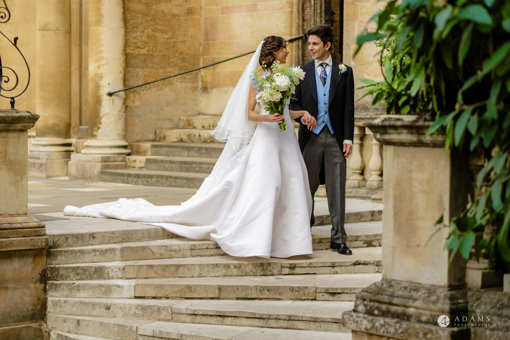 Trinity College Cambridge wedding married couple walk down the stairs