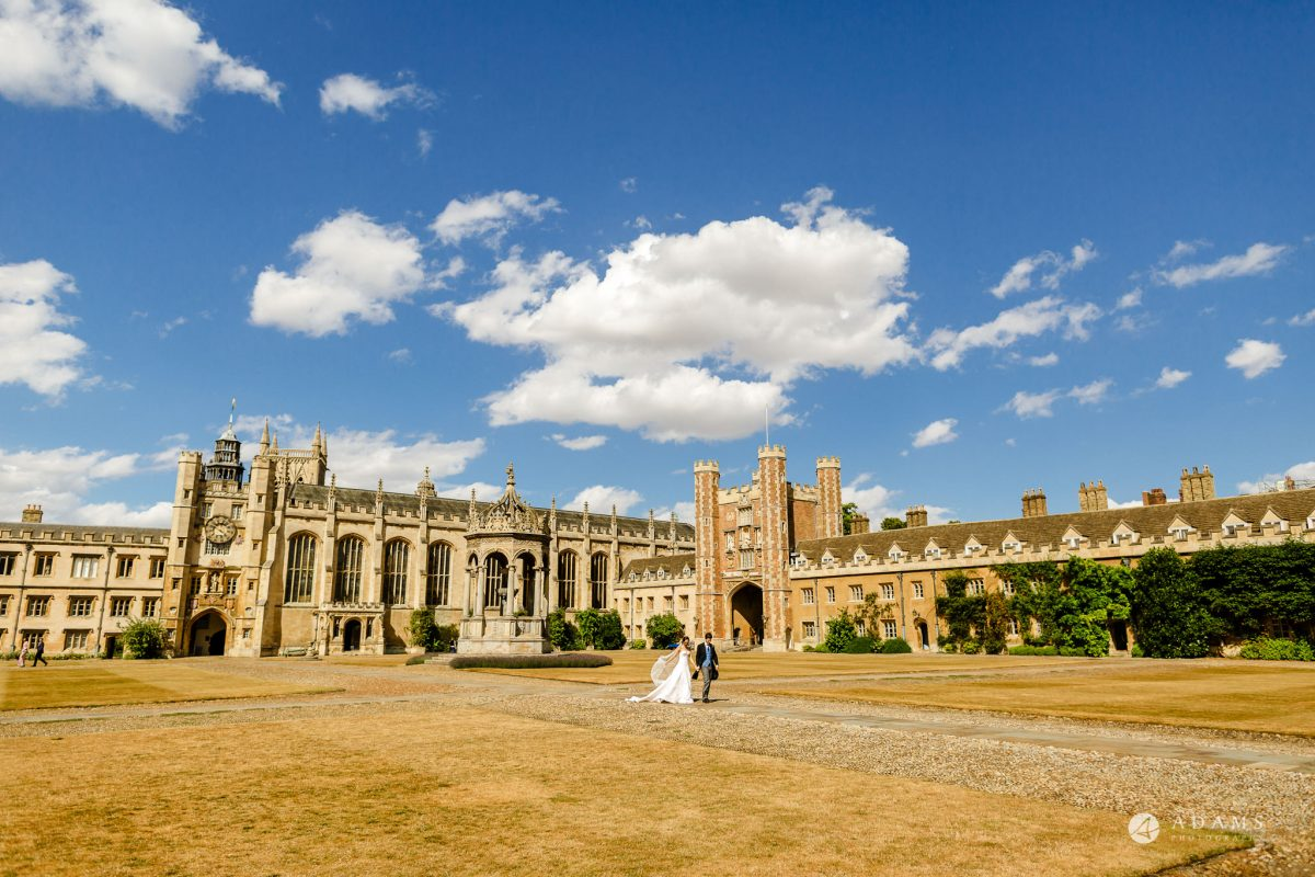 Trinity College Cambridge wedding bride and groom walk in the university courtyard