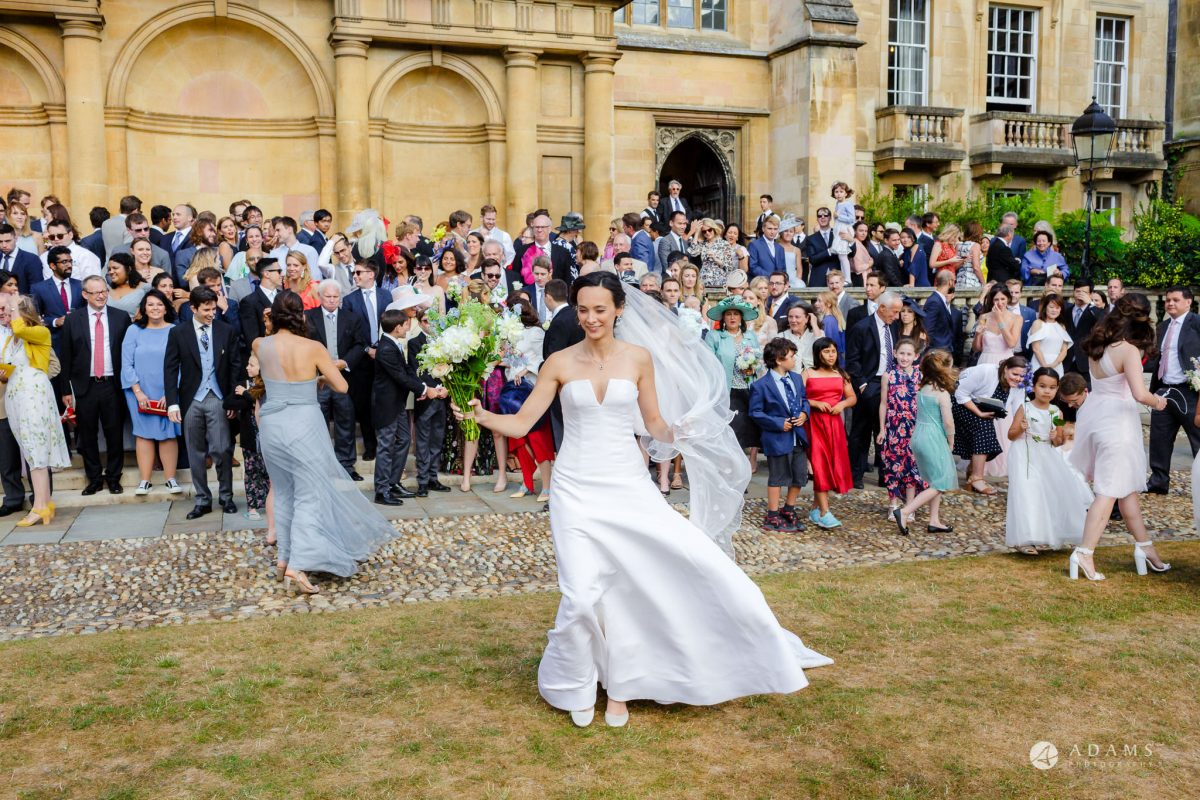 Trinity College Cambridge wedding bride in the wind
