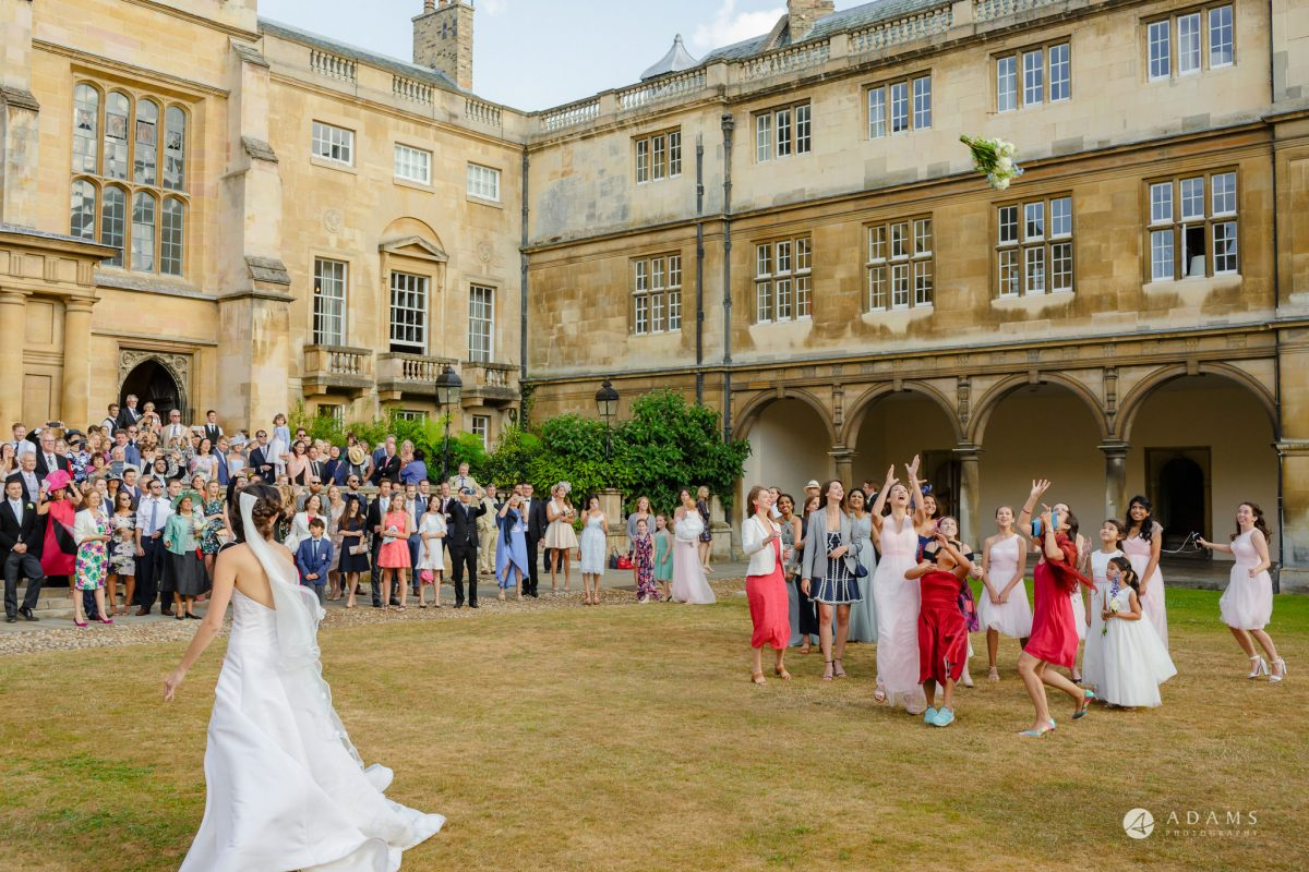 Trinity College Cambridge wedding bride throwing a bouquet