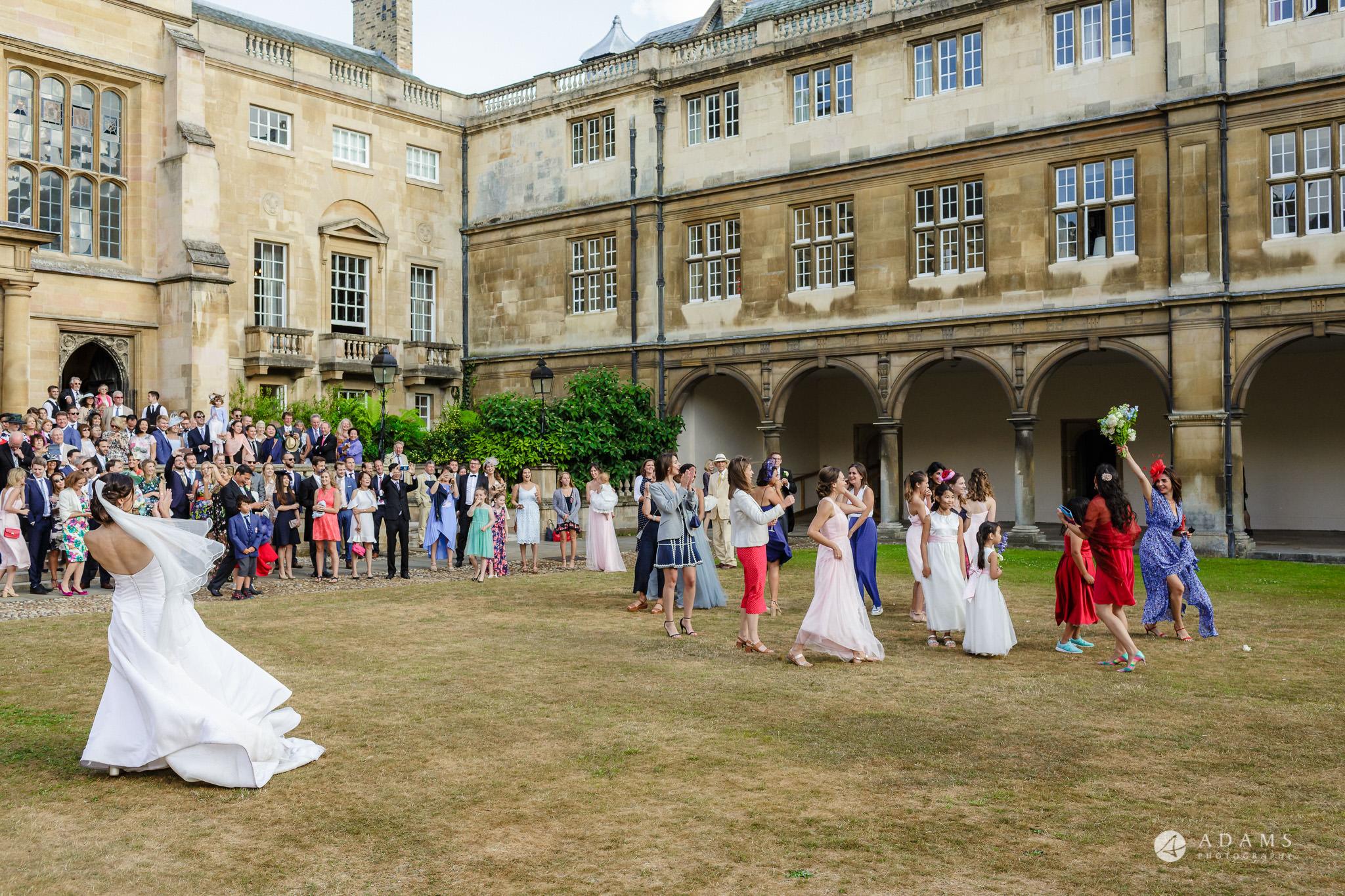 Trinity College Cambridge wedding brides friend catching a bouquet