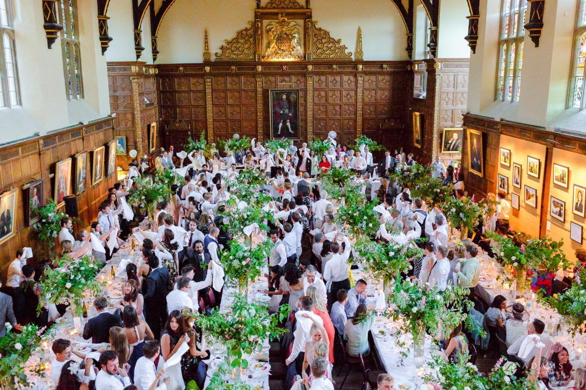Trinity College Cambridge wedding everyone holds hands in the air