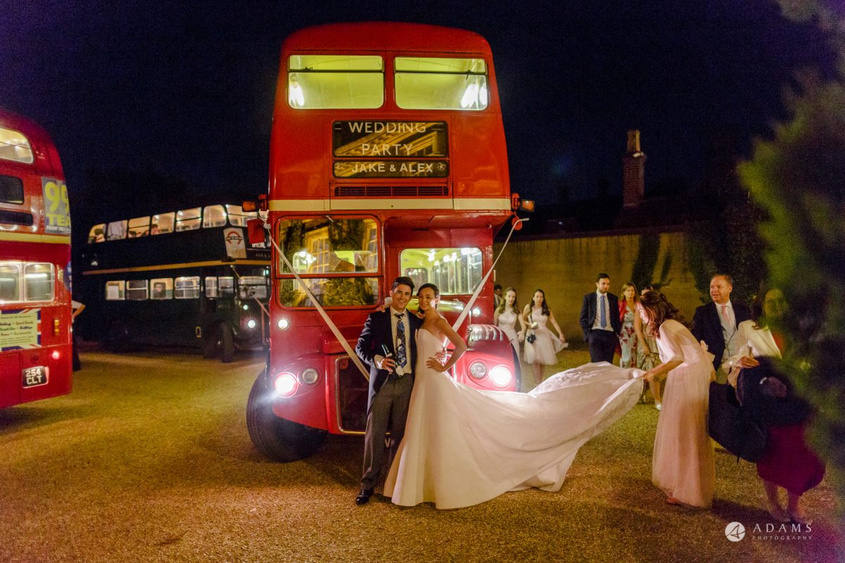 Trinity College Cambridge wedding groom and bride pose in front of the bus
