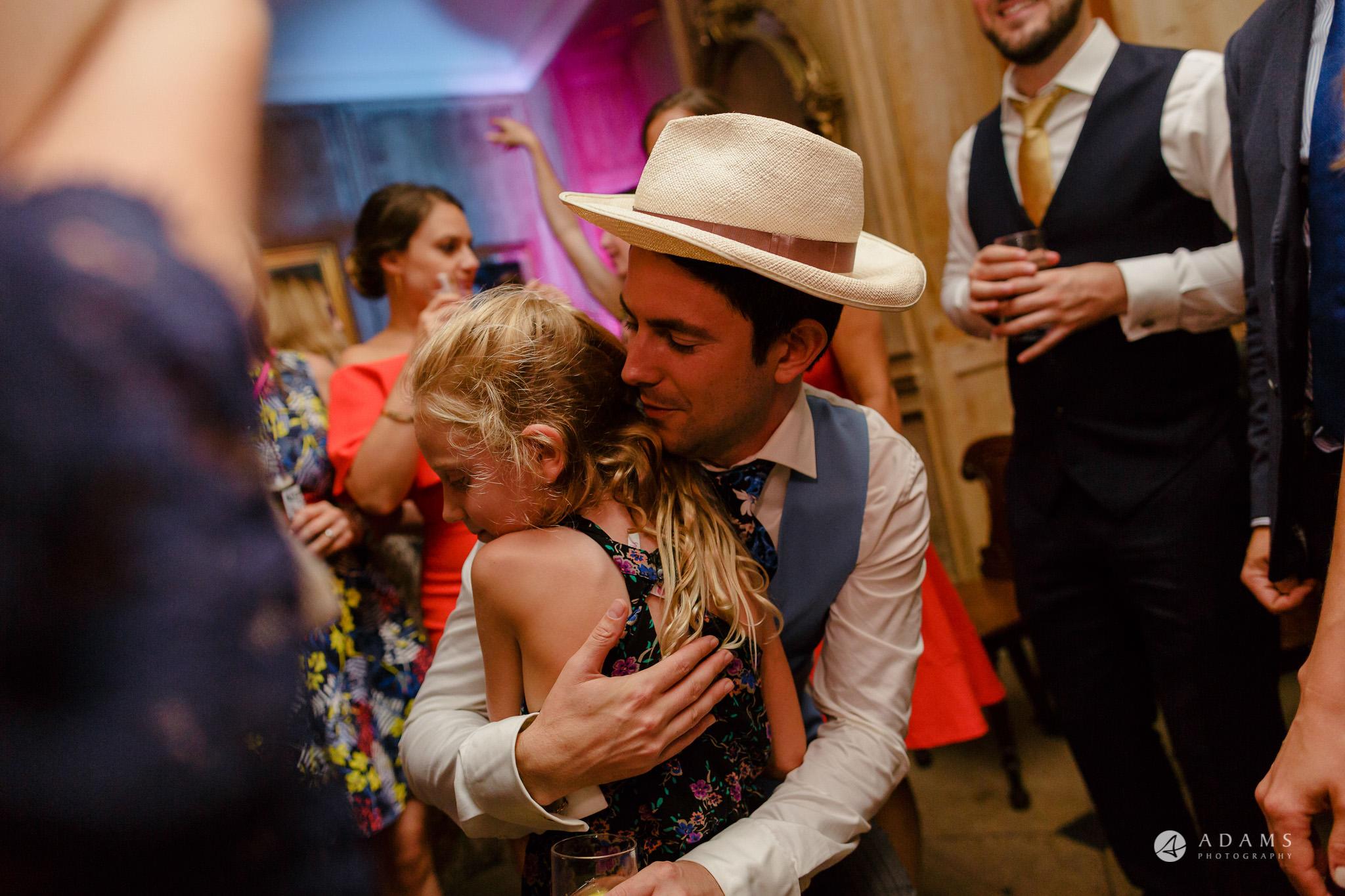 Trinity College Cambridge wedding groom hugs a kid