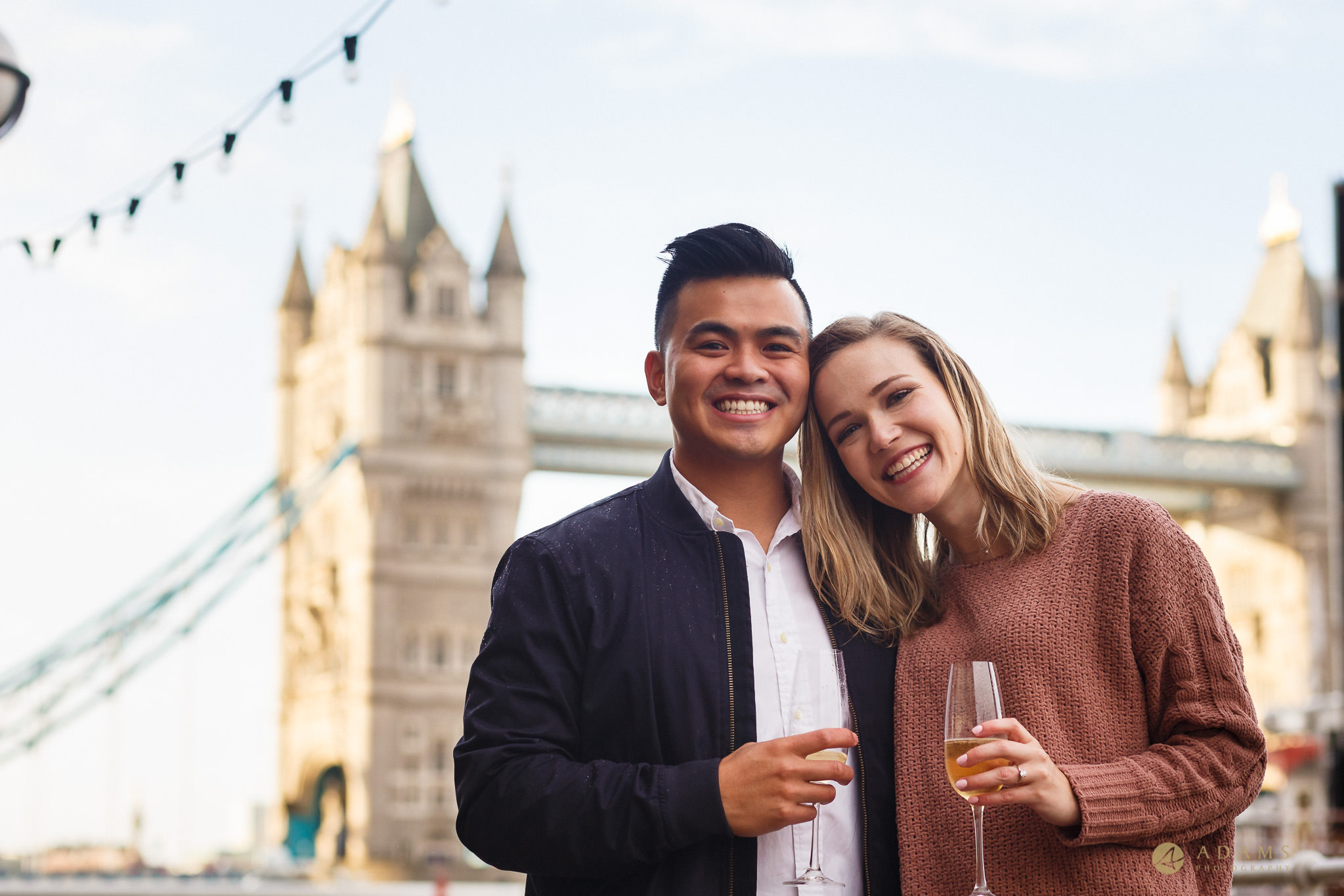 London Engagement Proposal Photographer Tower Bridge the couple drinking champagne