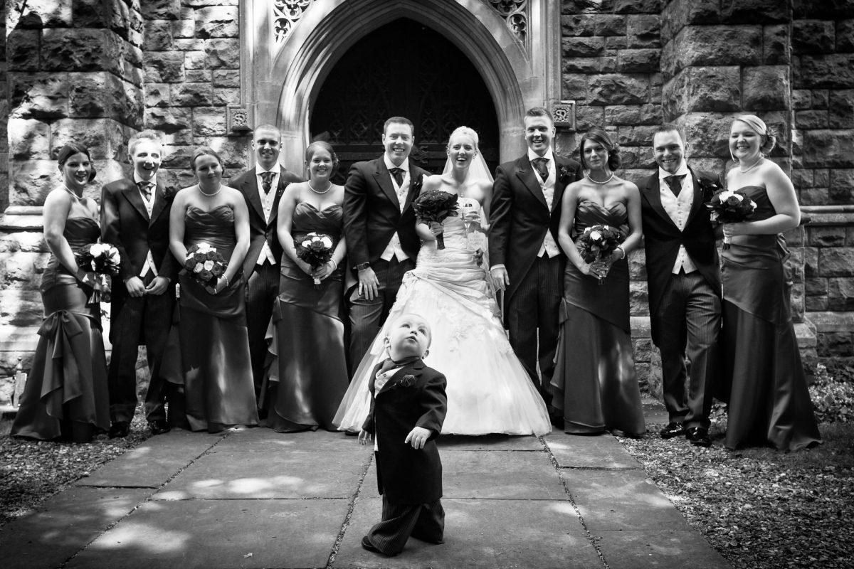 Buckinghamshire wedding photographer group photo in front of the church with a little kid