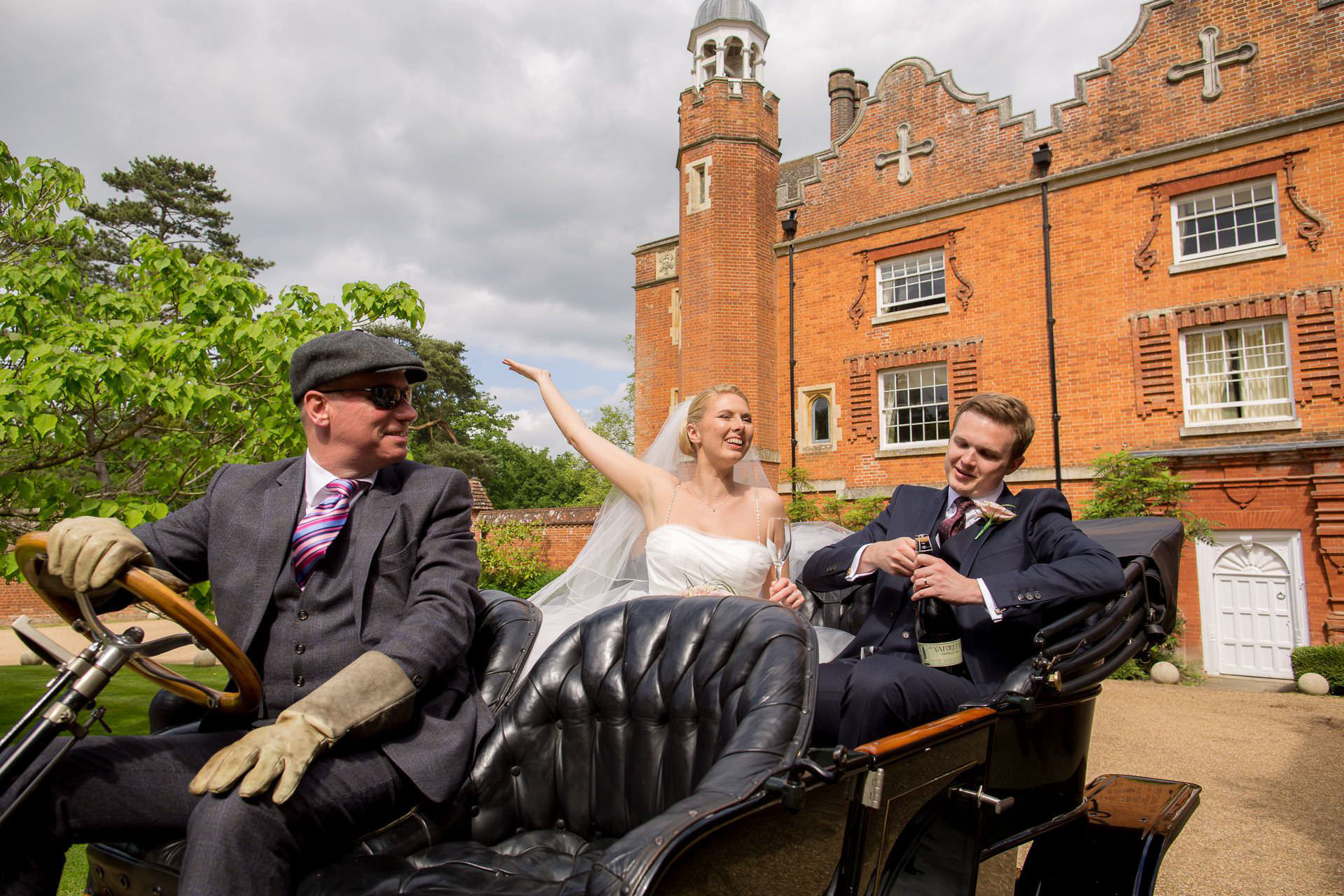 Surrey Wedding bride and groom drinking champagne on the vintage car