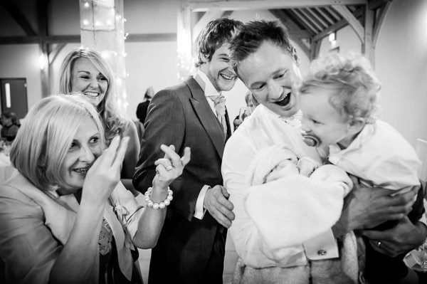 Mother of the groom is playing with grandson at a wedding