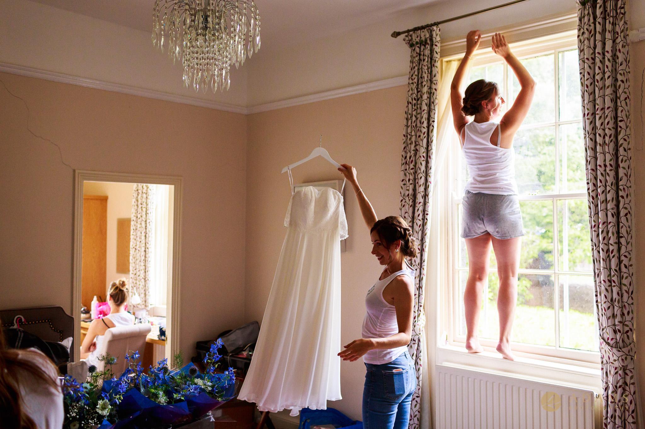 Wedding Photographer Cambridge bridesmaids hanging the dress
