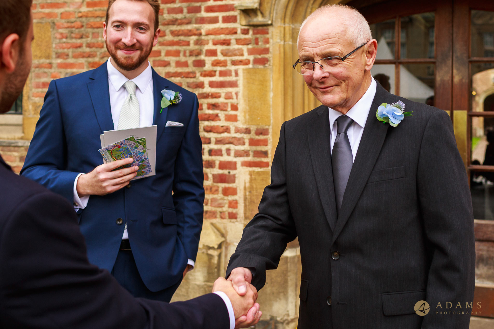 Wedding Photographer Cambridge father of the bride shale hands with the groom