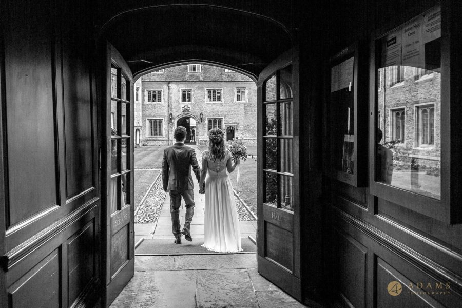 Cambridge Photographer bride and groom walk out through the doorway