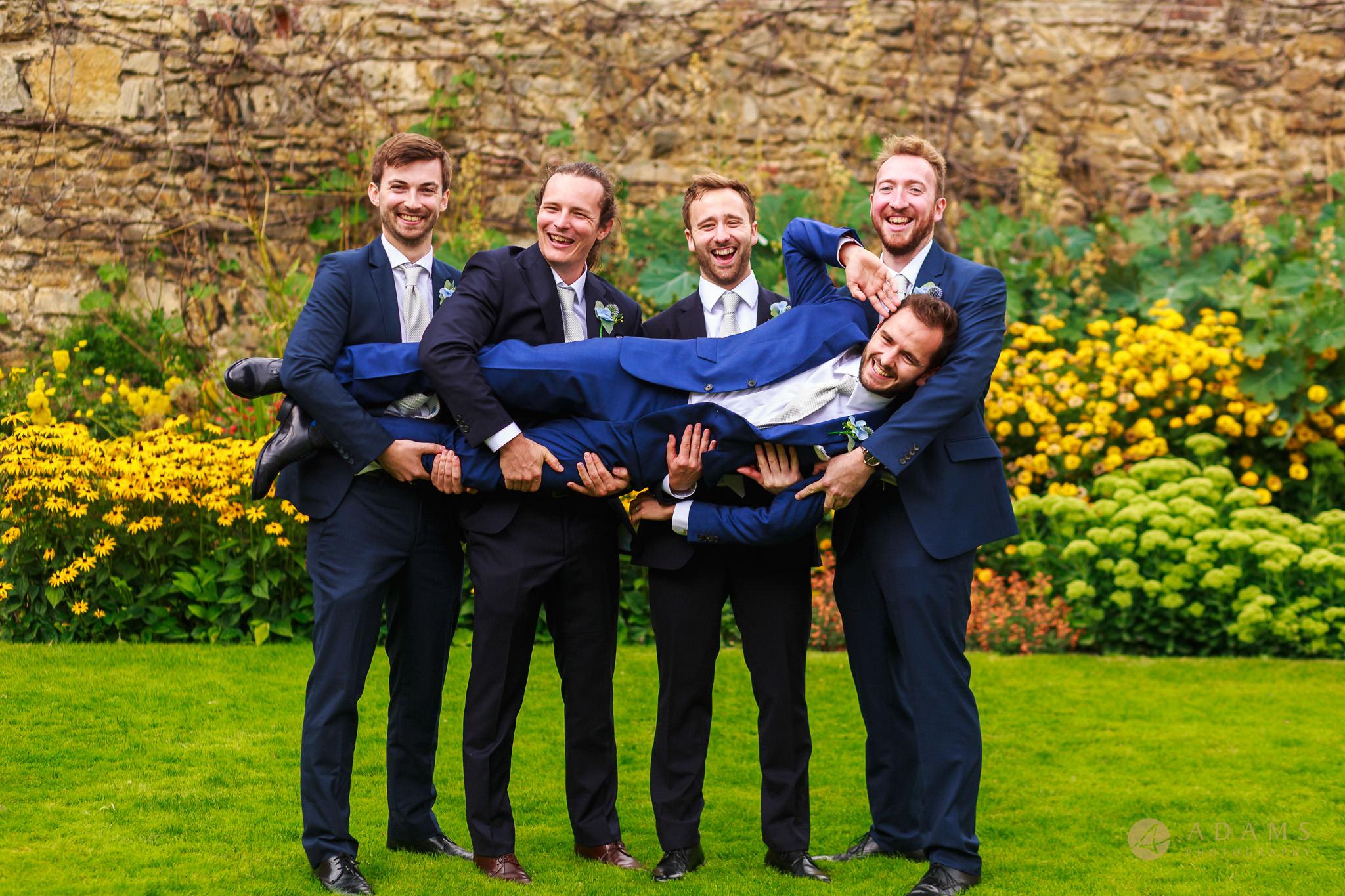 groomsmen hold the groom