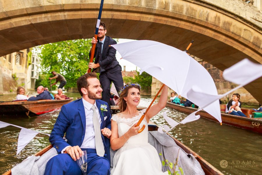 bride and groom holding umbrella while panting