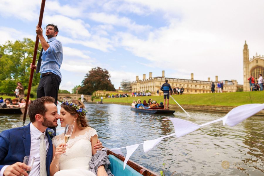 Cambridge Photographer groom and bride kissing while panting on the boat