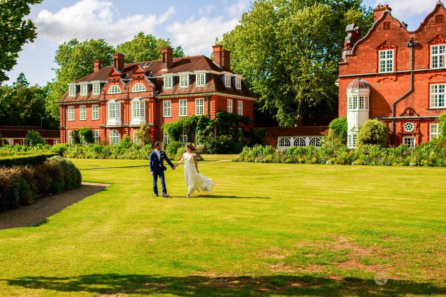 bride and groom walk on the grounds of Newnham College