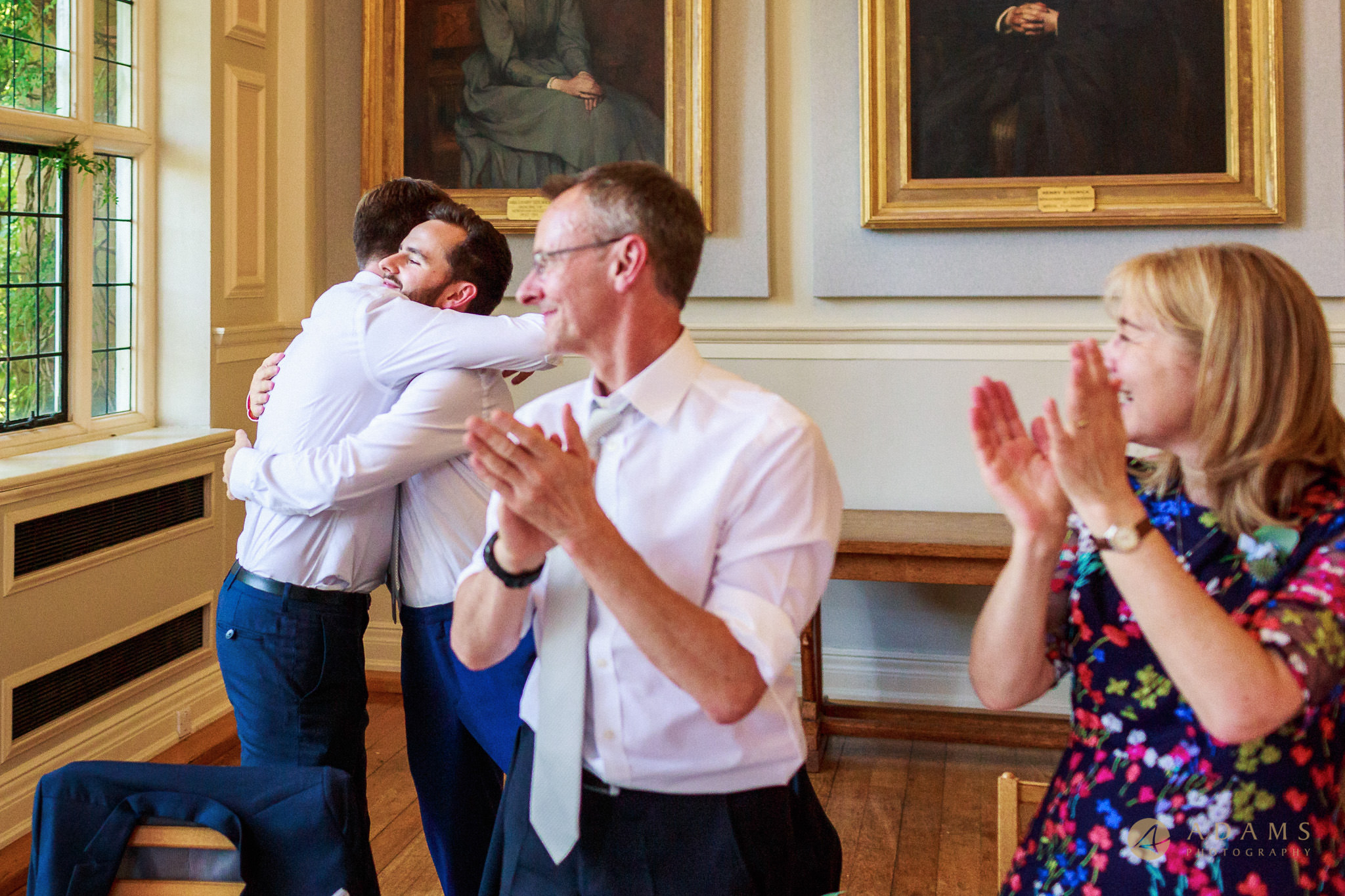 Wedding Photographer Cambridge groom hugs his bestman