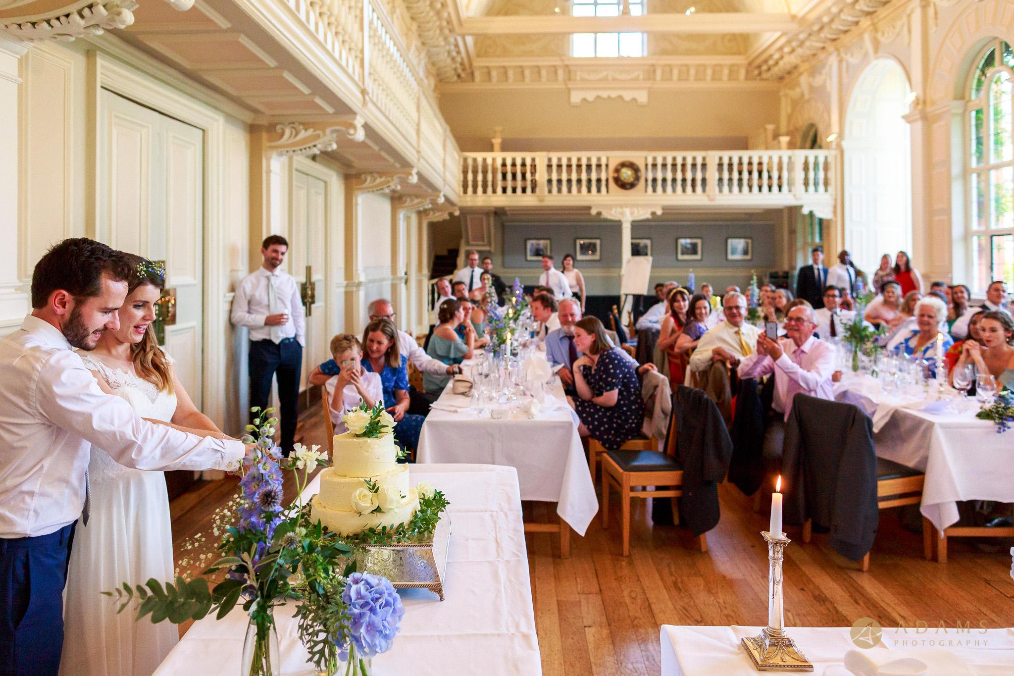 Wedding Photographer Cambridge cutting the cake at Newnham College