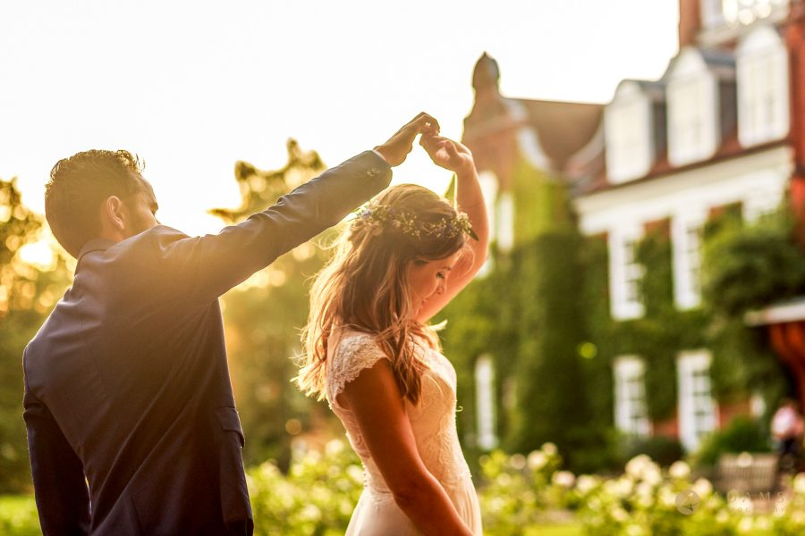 Wedding photographer Cambridge Newnham College couple dancing in the sun