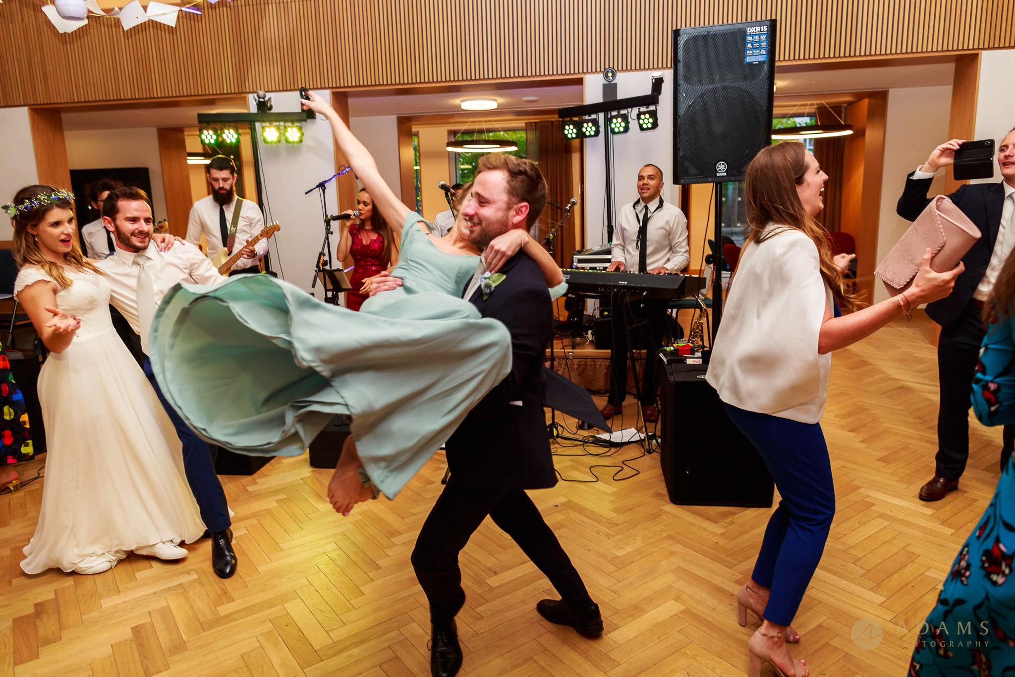 Wedding photographer Cambridge Newnham College guests dancing