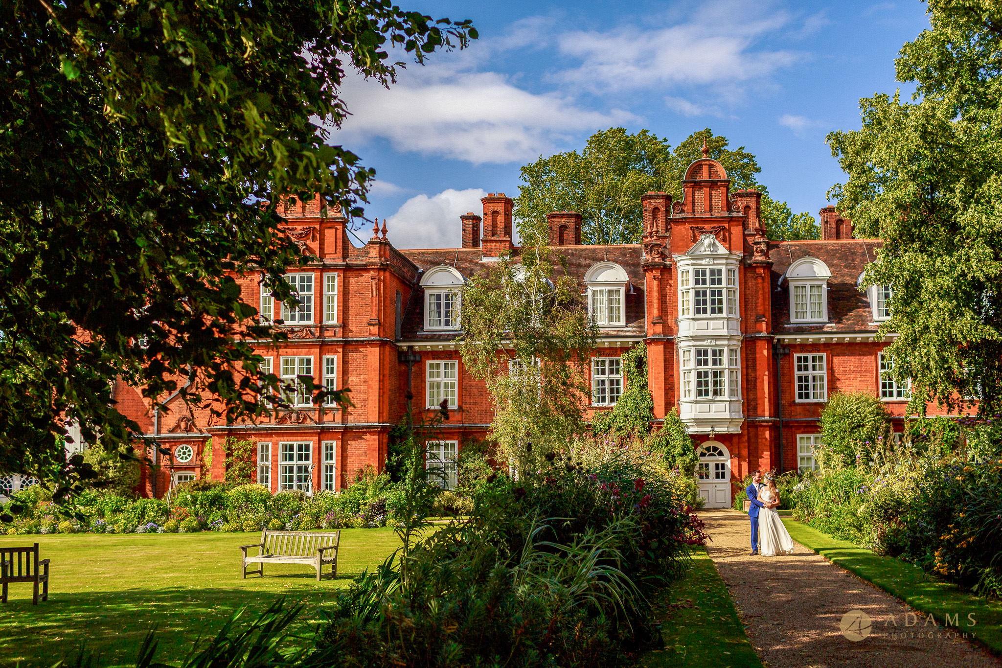 Wedding photographer Cambridge Newnham College portrait of the couple in front of the College
