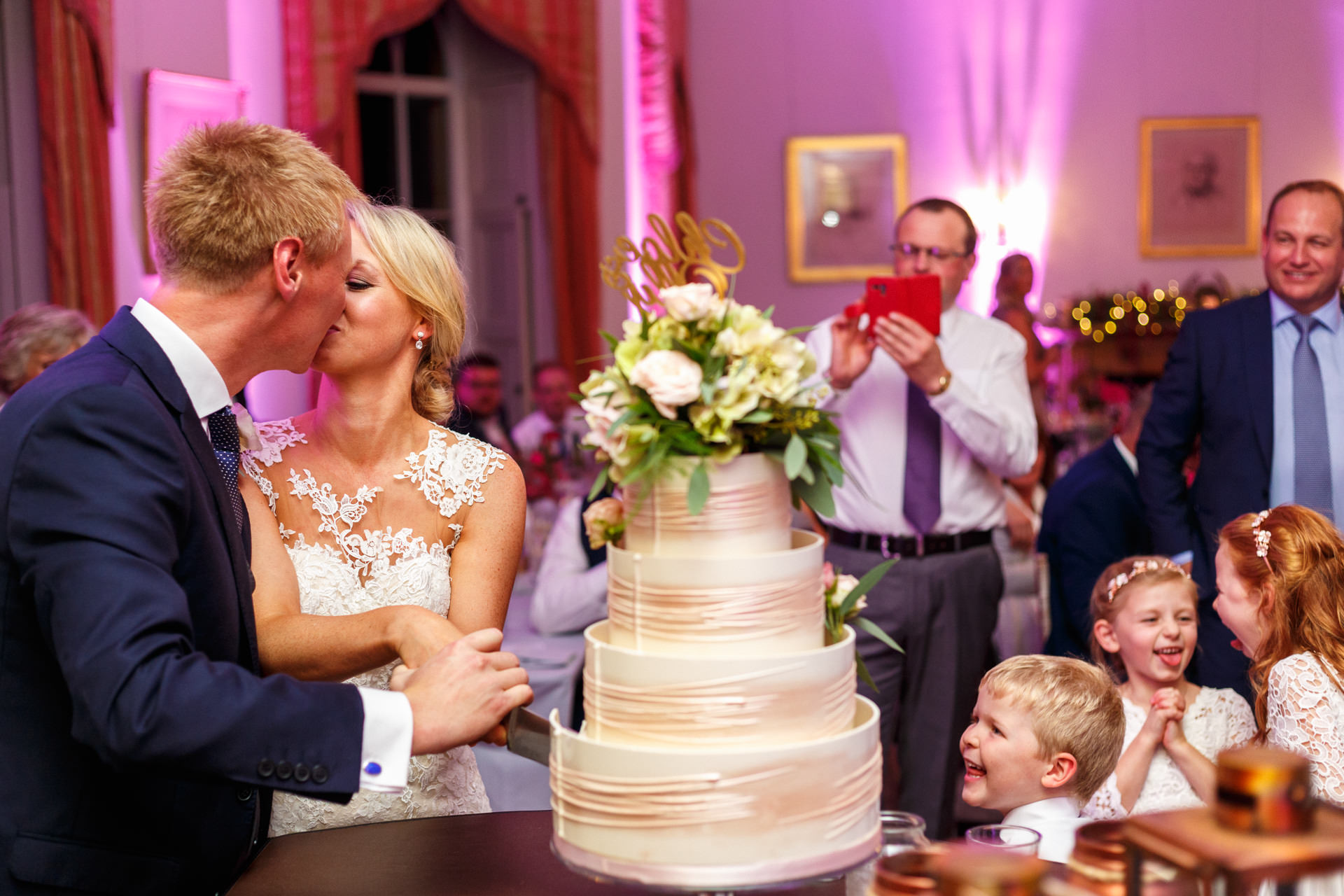 Couple kissing while cutting the cake