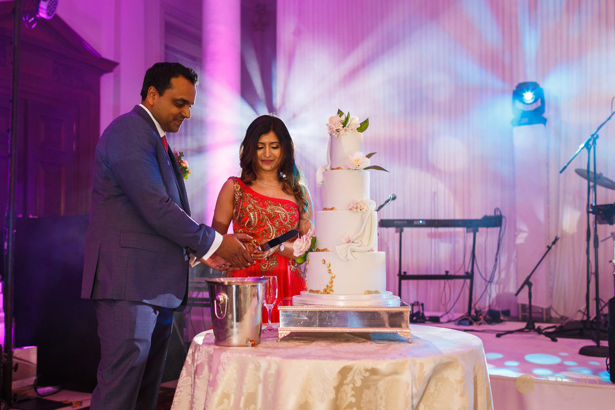 The Couple are cutting the cake at their wedding in Langham Hotel in London